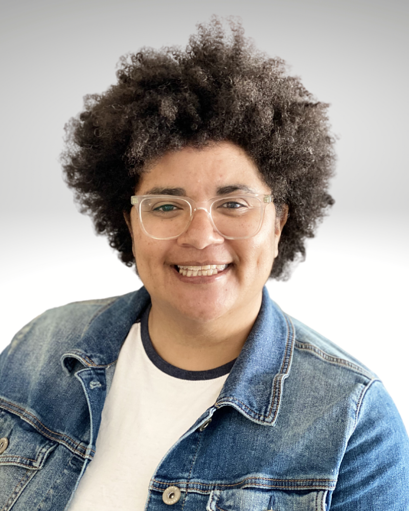 Light brown skinned woman with afro smiling