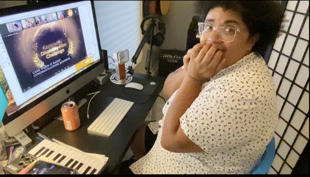A brown-skinned woman sits in a chair in front of her computer. She has glasses and a curly afro and is looking at the camera person with disbelief. Her computer screen has the logo for the Easterseals Disability Film Challenge on it. There are also several people on a Zoom call on the screen.