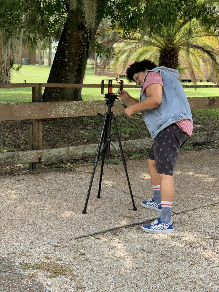 A brown skinned woman wearing a jean jacket vest, t shirt and shorts adjusts a tripod camera mount. She wears glasses and has a curly afro.