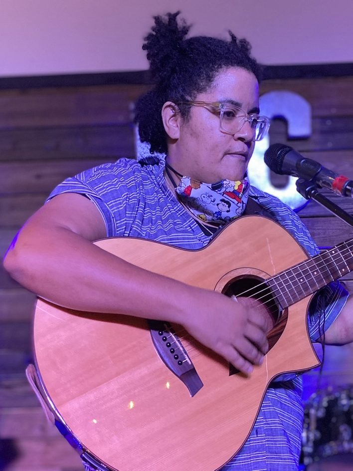 Jennifer Msumba, a brown skinned bi-racial woman standing on a stage and strumming a guitar with a pensive look on her face