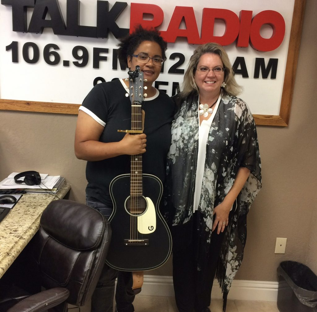 "Two women, Jennifer Msumba and Veronica Brandon Miller stand with their arms around each other in front of a sign that says ""Talk Radio 106.9 FM"". Jennifer is holding a guitar."