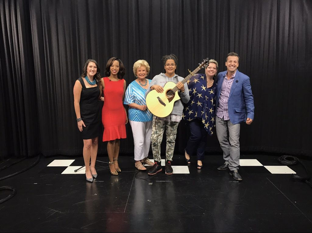 Six people of different genders, races and ages stand together smiling on set of the Suncoast View talk show. Jennifer Msumba is in the middle holding a guitar.