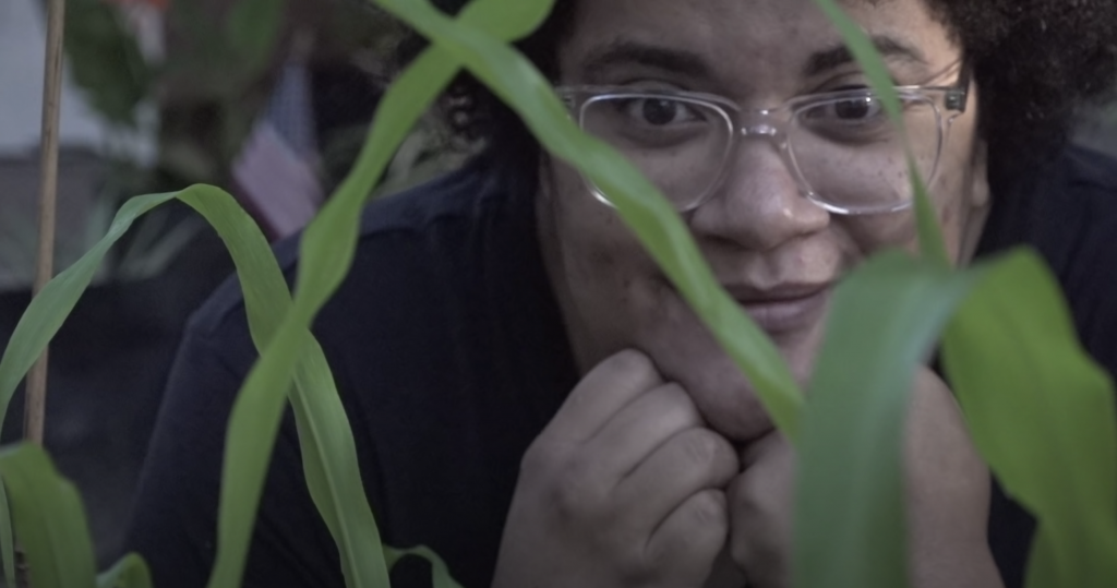 A brown skinned woman is kneeling down in front of the leaves of a corn plant. She is wearing glasses and has a curly afro.