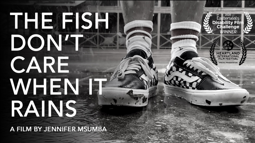 """The feet of a brown-skinned person standing in the pouring rain. They are wearing Vans sneakers. The text on the photo says """"The Fish Don't Care When It Rains"""" """"A Film by Jennifer Msumba"""""""
