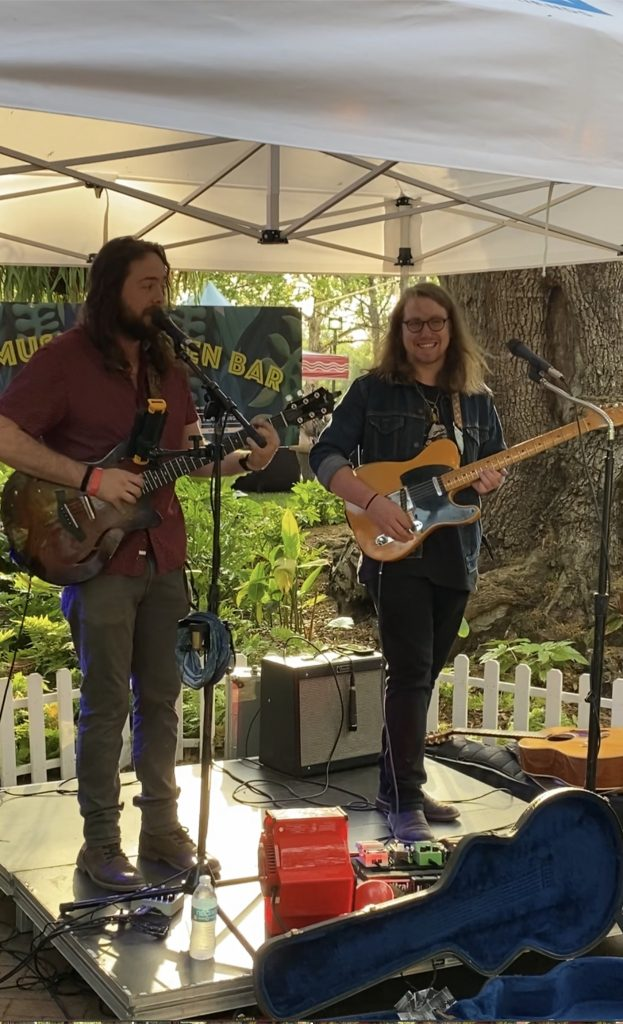 Two men with long hair standing on a small stage outside and playing electric guitars. One is wearing glasses. They have an open guitar case in front of them to collect tips.