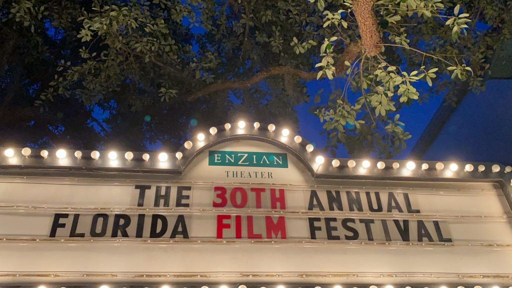 "A movie theater sign trimmed with lights that says ""The 30th Annual Florida Film Festival"" There is a night sky behind the sign and also an oak tree branch."